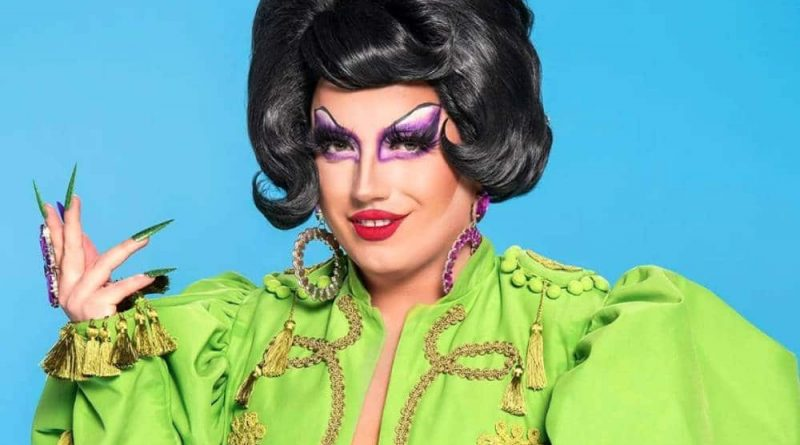 A promotional photo of Drag Race UK series three contestant Choriza May in a green outfit with a beautiful black wig and sharp acrylic nails